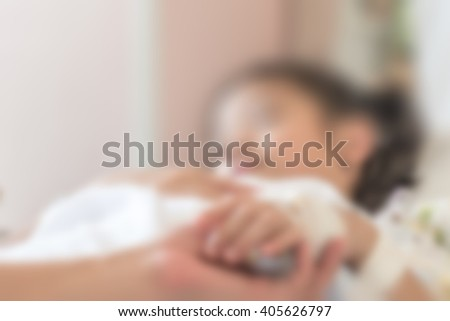 Blurred abstract background of young Asian girl kid patient sleeping recovery in hospital bed in ward room with family caregiver/ nurse supportive helping hand support: Nursing caretaker concept  - stock photo