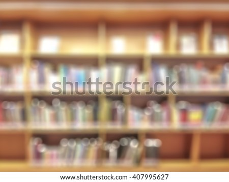 Blurred abstract background view of university/ school public library wall aisle of book shelves no student: Blurry interior perspective indoor study room with furniture & stacks of books  - stock photo