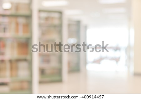 Blurred abstract background view of university student girl behind aisle of book shelves in school library: Blurry interior perspective indoor study room with tables, chairs, seats & stacks of books - stock photo