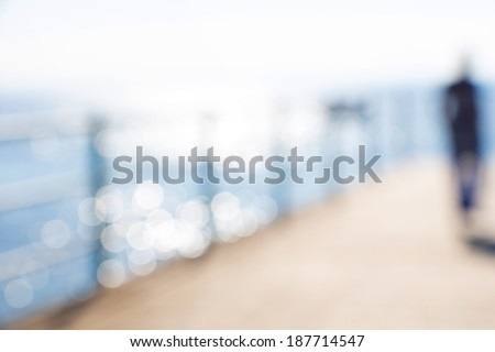 Blurred abstract female figure with sea background and bokeh - stock photo