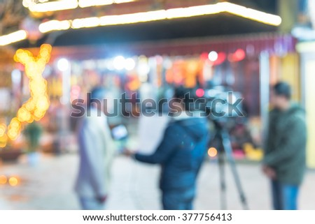 Blurred abstract of cameraman recording/videotaping a male journalist interviewing with local people at a pagoda in Ha Giang, Viet Nam. Colorful bokeh Lunar New Year decoration light is in background. - stock photo