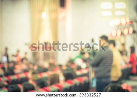 Blurred abstract of cameraman recording/videotaping an event in Hanoi, Vietnam. Campus lecture hall with full of audience in line of red armchairs rows. Vintage vignette added. - stock photo