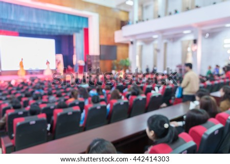 Blurred abstract of cameraman recording/videotaping an event in the university hall in Hanoi, Vietnam. Campus lecture hall with full of audience in line of red armchairs rows. Blur people background. - stock photo