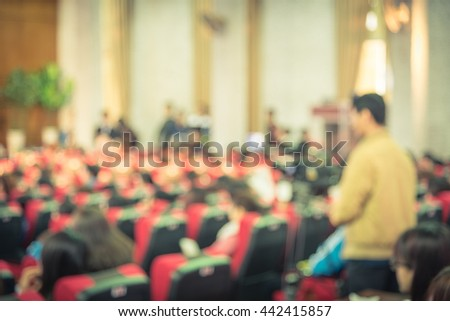 Blurred abstract of cameraman recording/videotaping an event in the university hall in Hanoi, Vietnam. Campus lecture hall with full of audience in line of red armchairs rows. Vintage vignette added. - stock photo