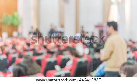 Blurred abstract of cameraman recording/videotaping an event in the university hall in Hanoi, Vietnam. Campus lecture hall with full of audience in line of red armchairs rows. Blur people in panoramic - stock photo