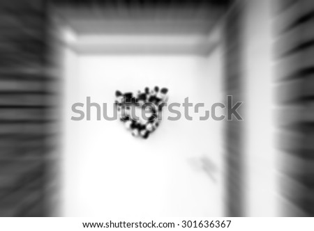 Blurred abstract photo of wedding (or birth) flower wreath in heart shape on door. Aged photo. Black and white. - stock photo