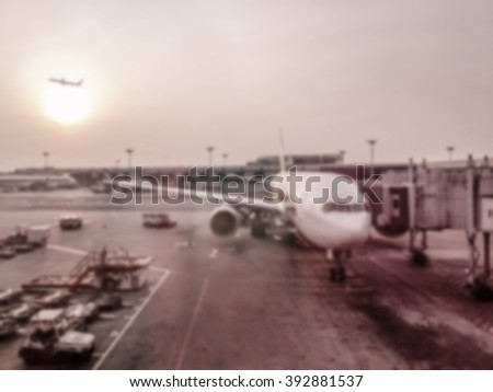blurred airport, airport runway, air plane ready to take off and airplane in the background with the sun. big close up airplane with workers in an airport runway - stock photo