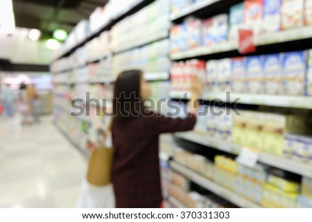 blurred asian woman choosing goods on shelves in supermarket:blur people buyer checking price in local market on weekend concept:blur girl shopping at market store center on vacation conceptual. - stock photo