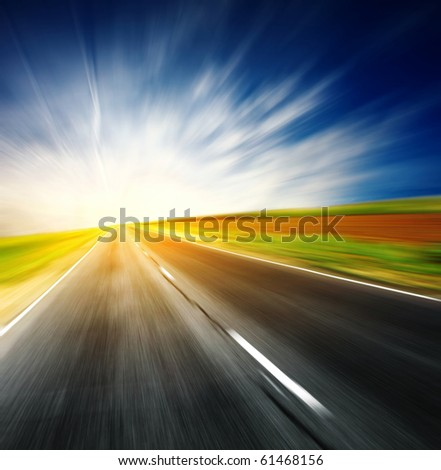 Blurred asphalt road and blue sky with clouds and light - stock photo
