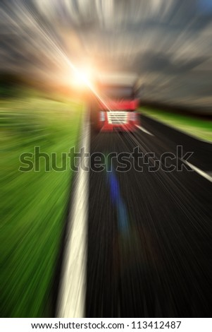Blurred asphalt road and clouds over it with truck - stock photo