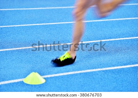 Blurred athlete by a slow camera shutter speed competing on blue sprint track - stock photo