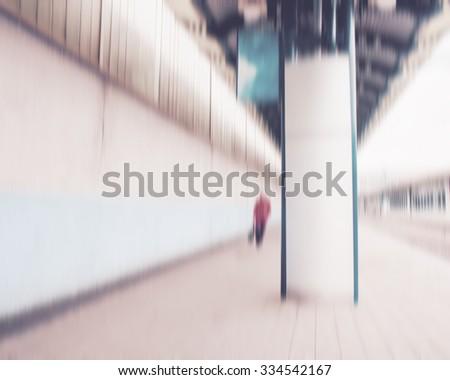 blurred background, a woman walking along train station platform - stock photo