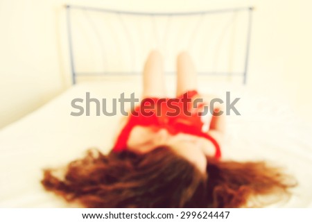 blurred background beautiful woman with long hair and beautiful red underwear,woman lying on the bed - stock photo