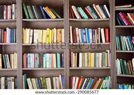 blurred background. bookshelf in public  library - stock photo