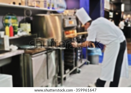 Blurred background - Chef puts pizza into the oven. - stock photo