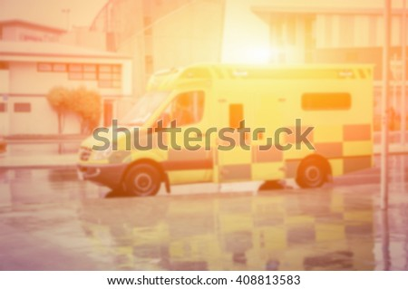 blurred background of An ambulance speeding through the streets.in vintage color effect. - stock photo