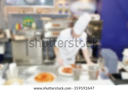 Blurred background of chef preparing a pizza. - stock photo