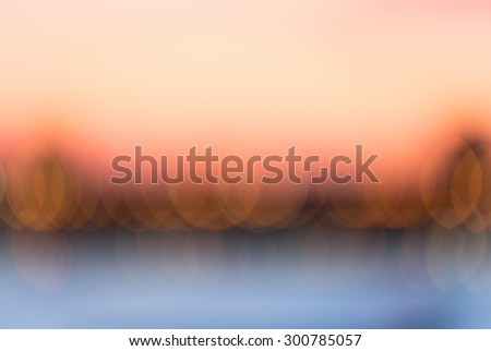 Blurred background of city at sunset. Modern, abstract bokeh of landscape with water at sunrise. Hazy background with vivid an vibrant warm colors and cool contrast.  Image with peaceful, calm energy. - stock photo