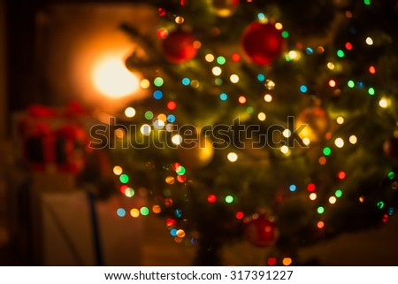 Blurred background of decorated glowing Christmas tree and fireplace - stock photo