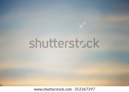 blurred background of evening city space sky with sunshine flare lights.blur vintage warm tone backdrop concept.shimmer glint shine illuminated sun ray.soft clouds dusk canopy of dream display. - stock photo