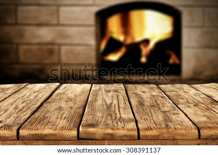 blurred background of fireplace and big shabby wooden table  - stock photo