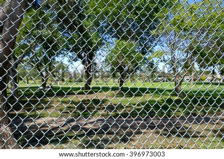 blurred background of golfers on course behind fence                               - stock photo
