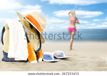 blurred background of summer coast and woman in pink bikini with travel time and bag  - stock photo