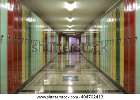 Blurred background of tunnel-like hallway lined with multi-colored lockers. - stock photo
