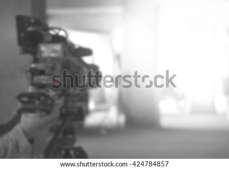 blurred background of videographer working wiht Professional equipment video camera  shooting movie cinema video for broadcast TV television with red light - stock photo