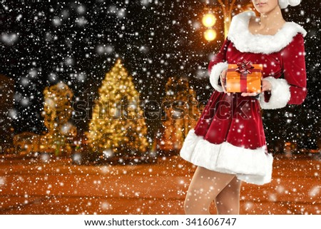 blurred background of winter night and red woman and golden box of gift  - stock photo