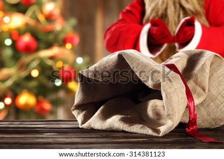 blurred background of xmas tree in home and red santa claus with open sack of brown color  - stock photo