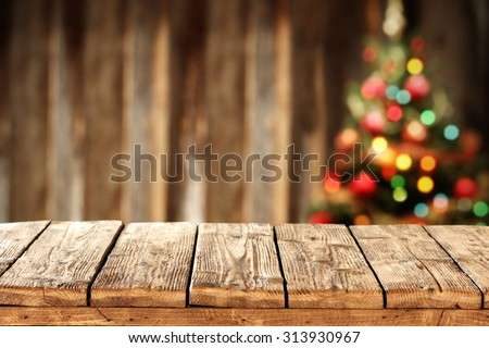 blurred background of xmas tree lights and wall with free space on wooden worn table  - stock photo