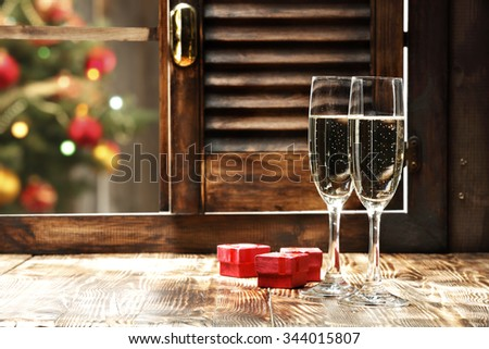 blurred background of xmas tree lights and window of champagne and red boxes  - stock photo
