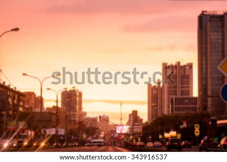 Blurred background: street with road, cars, lights, signs etc on the sunset in Moscow, Russia. Image with toning - stock photo