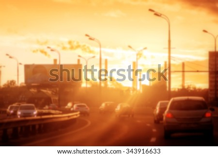 Blurred background: street with road, cars, pedestrian, crosswalk, traffic lights, signs etc on the sunset with beautiful sun rays in Moscow, Russia. Image with toning - stock photo