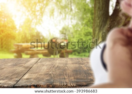 blurred background with young woman and closeup of table  - stock photo