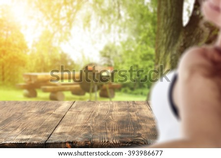 blurred background with young woman and deck of wood and grill time  - stock photo