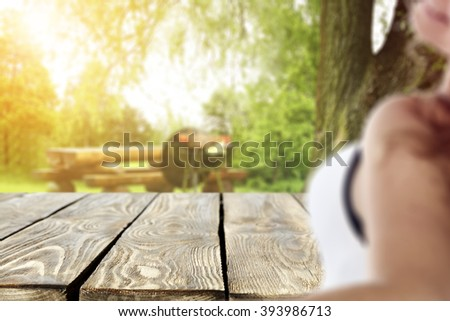 blurred background with young woman and table and garden  - stock photo