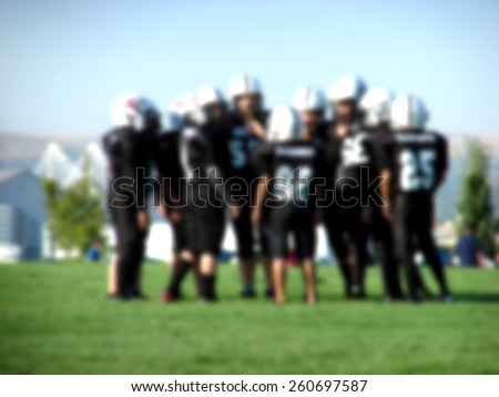 blurred background with youth american football players in action                               - stock photo
