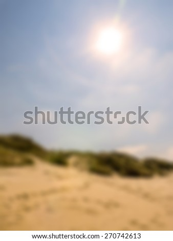 Blurred beach dunes with sun and flare in sky - stock photo