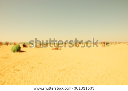 Blurred beach photo. People relaxing on beach. Vacation background (Trouville-sur-Mer, Normandy, France) Retro aged photo.  - stock photo