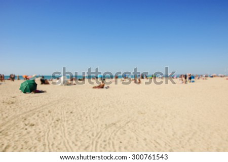 Blurred beach photo with selective focus on green umbrella. People relaxing on beach. Vacation background (Trouville-sur-Mer, Normandy, France)  - stock photo