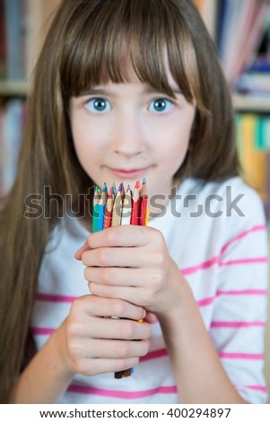 Blurred beautiful girl holding many pencils with selective focus only on pencils. Concept: the colored pencils improve the creativity in children - stock photo