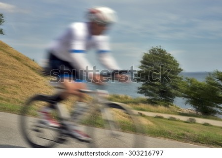 Blurred bike race cyclists at high speed close to the beach in Fredericia, Denmark - stock photo