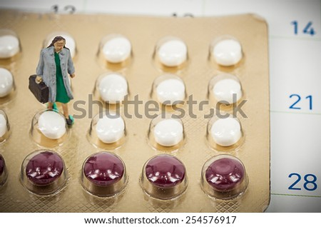 blurred , birth control pills with miniature doctor woman. abstract background to solution of birth control. - stock photo