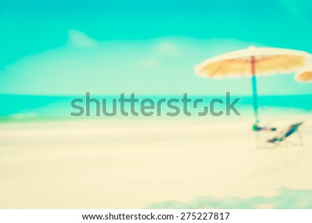 Blurred blue sea and white sand beach with parasol and beach chair, summer and holiday background concepts - vintage tone - stock photo