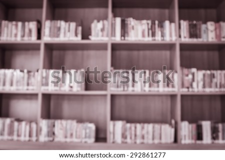 Blurred books on the shelf in public library in vintage color tone for background - stock photo