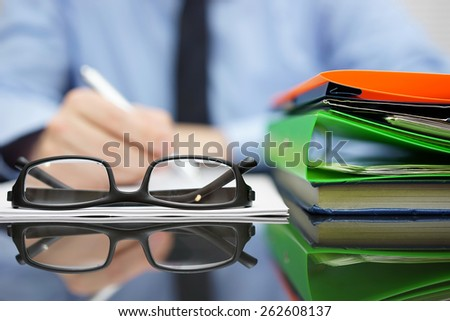Blurred Businessman is writing document, focus on glasses and folders - stock photo