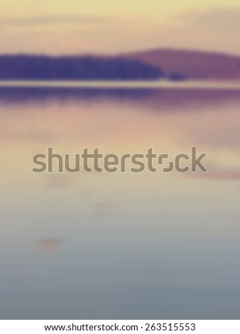 Blurred calm lake with reflected forest and hills in the distant background. Designed to work with text overlays including the text colour white. Artistic intent with filters and desaturation.  - stock photo