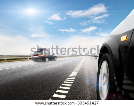 Blurred car on icy road with sky - stock photo